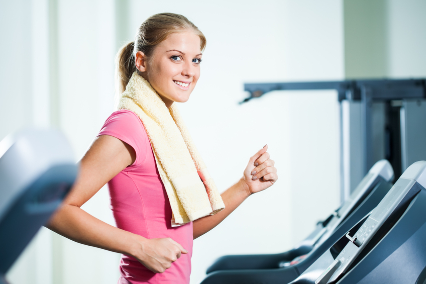 Happy girl exercising in gym